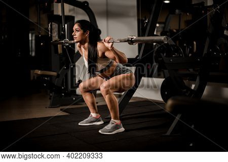 Beautiful Strong Muscular Woman Bodybuilder With Barbell Doing Squats In Gym.