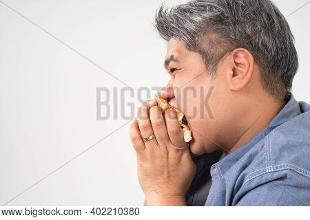 Asian Middle Aged Man Holds And Eating A Hamburger Deliciously Concept Of Binge Eating Disorder (bed