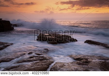 Coastal Sunrise Waves Crashing Onto Rocks And Flowing Fast In All Directions Back To The Sea