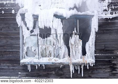Frozen And Broken Window Of An Old Wooden Residential Building Close Up