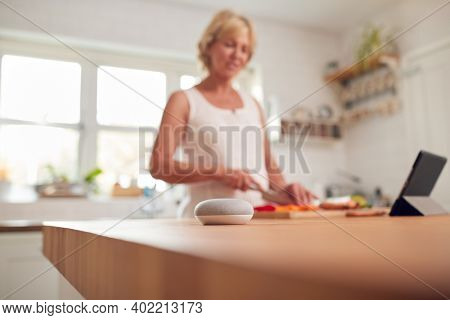 Retired Woman Making Meal In Kitchen With Smart Speaker In Foreground