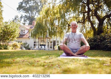 Senior Man At Home In Garden Wearing Fitness Clothing Sitting On Yoga Mat And Meditating
