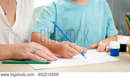 Closeup Video Of Teacher Teaching Drawing And Painting Little Boy With Pencil. Mother Educating And