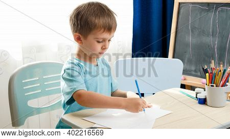Concentrated Little Boy Drawing Or Writing With Pencil While Sitting Behind School Desk At Home Or S