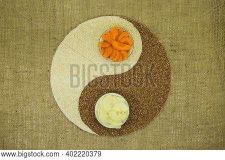The Concept Of Yin Yang. Sign Yin Yang Against The Background Of Burlap. Rice, Buckwheat, Carrots An