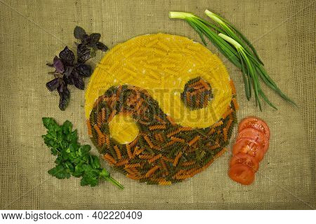 The Concept Of Yin Yang. Sign Yin Yang Against The Background Of Burlap. Colored Pasta With Natural