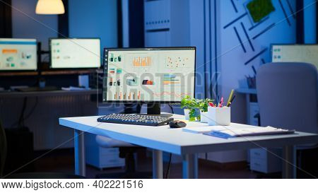 Empty Start Up Business Office With Modern Design During Night With Graphics Running On The Desktop.