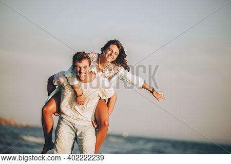 Young Man Giving Piggyback Ride To Girlfriend On Beach.