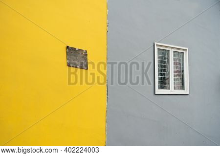 Old Wall With Window Painted In Yellow And Gray Colors