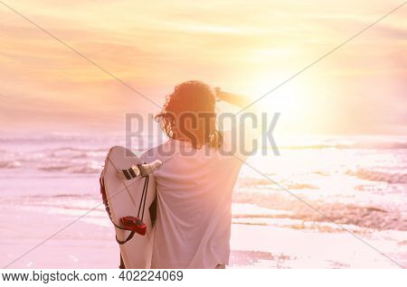Surfer Man With Surfboard Walking By Water Looking At Waves At Sunrise Or Sunset. His Long Hair Flyi
