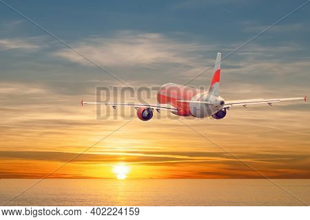 Airplane Flying Above Sea Skyline At Sunset. Back View.  Empty Place For Text, Copy Space.