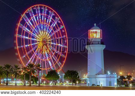 Ferris Wheel At Amusement Park At Night. Batumi Boulevard.  Photo Is Taken With A Long Exposure And