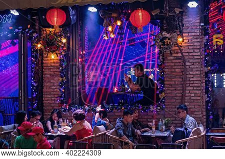 Night Bar With People. Night Life At Famous Tourist Walking Street Bui Vien During Lockdown.  Defocu