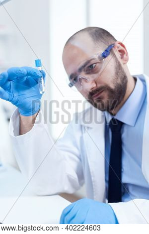 Male Scientist With Sterile Gloves Looing At Test Tube With Genetic Material. Researcher In Biotechn