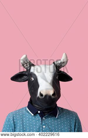 portrait of a man wearing a cow mask on a pink background with some blank space on top