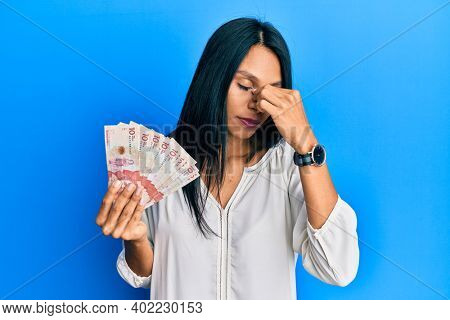 Young african american woman holding 10 colombian pesos banknotes tired rubbing nose and eyes feeling fatigue and headache. stress and frustration concept.