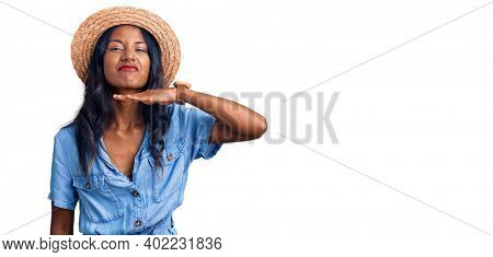 Young indian girl wearing summer hat cutting throat with hand as knife, threaten aggression with furious violence