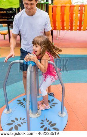 Man Dad Plays With Daughter, Girl 5-6 Years Old, Summer City On Sports Playground. Emotion Of Joy, F