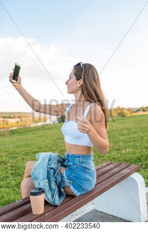 Womanish Girl City Summer, Sits Bench And Takes Pictures Smartphone, Online Recording On Internet, A
