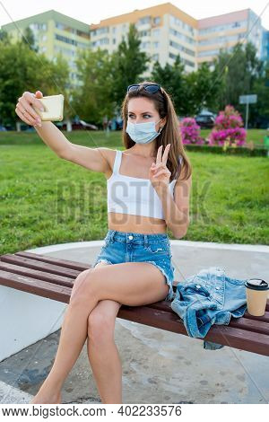 Female Woman In City Summer In Medical Mask, Sits On Bench Pictures Smartphone, Online Recording On
