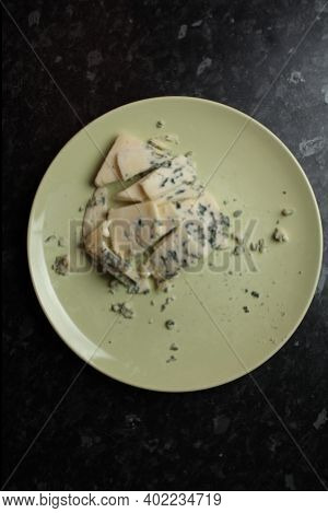 Blue Cheese With Mildew On A Light Plate On Black Background. Blue Cheese. Cheese With Edible Mildew