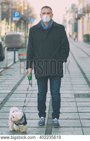 Man on a walk with a small maltese dog in a city street