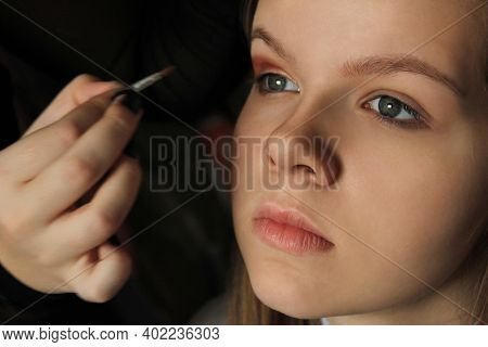 Applying Eyeshadow On A Beautiful White Caucasian Girl, Model With Perfect Healthy Skin. Professiona