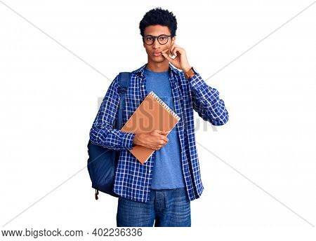 Young african american man wearing student backpack holding book mouth and lips shut as zip with fingers. secret and silent, taboo talking