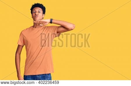Young african american man wearing casual clothes cutting throat with hand as knife, threaten aggression with furious violence