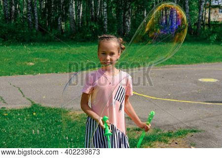Girl Playing With Giant Soap Bubbles Outdoors. Birthday Activity For Kids. Happy Girl Holding Soap B