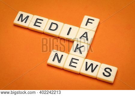 media and fake news crossword in ivory letter tiles against textured handmade paper, information and communication concept