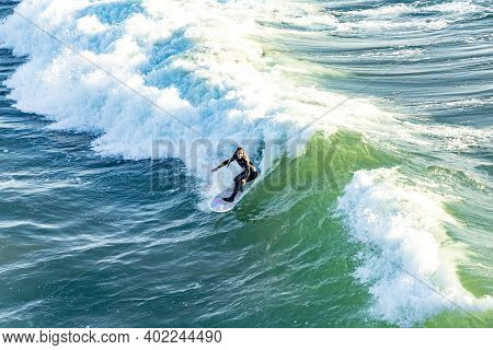 Manhattan Beach, Usa - March 4, 2019: Surfer Enjoys The Waves At Manhattan Beach Near Los Angeles.