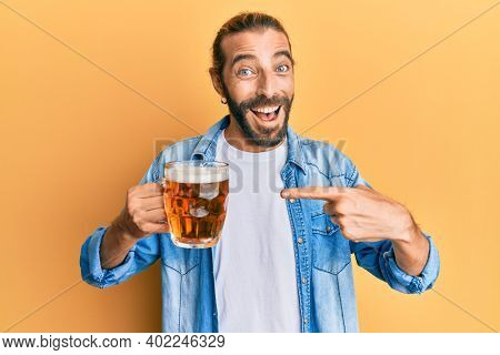 Attractive man with long hair and beard drinking a pint of beer smiling happy pointing with hand and finger