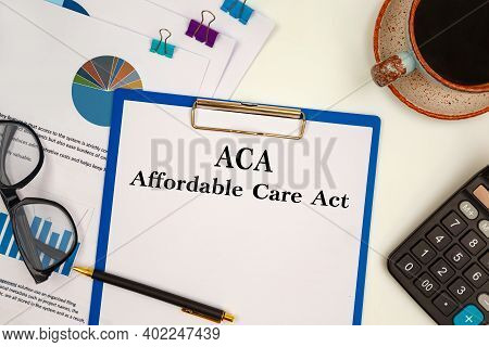 Paper With Aca Affordable Care Act On The Office Table, Calculator And Glasses