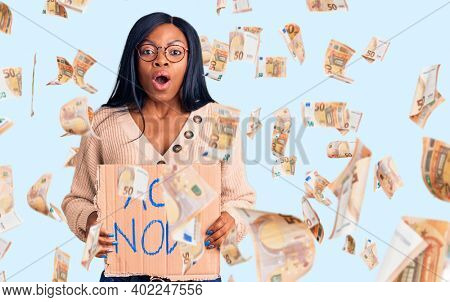 Young african american woman holding act now banner scared and amazed with open mouth for surprise, disbelief face