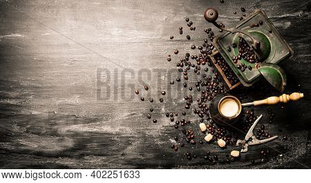 Fresh Brewed Coffee Pot And An Old Coffee Grinder With Roasted Beans. On Black Rustic Background.