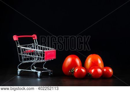 Shot Of Ripe Tasty Tomatoes In Shopping Cart Or Trolley On White Background. Tomato Trading Concept.