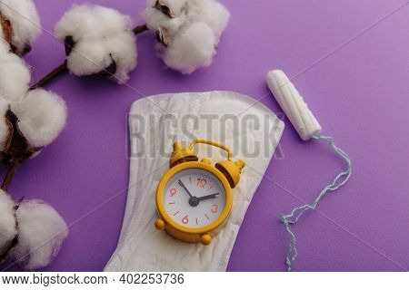 Daily Sanitary Pads, Tampon And Yellow Alarm Clock Close-up. Hygiene Protection For Woman Critical D