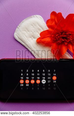 Menstruation App Calendar In Smartphone With Sanitary Pad, Pills And Red Flower On A Lilac Backgroun