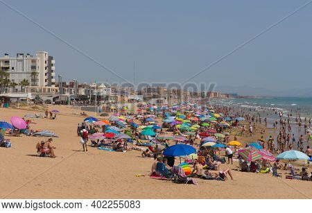 The Beach Packed With Umbrellas To Protect Holidaymakers From The Heat Of The Summer Sunshine In Tor