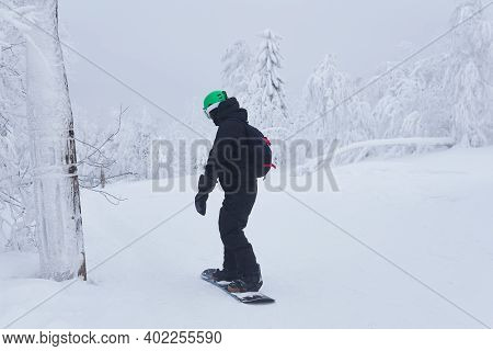 Teenage Snowboarder Going To Slide Down A Mountain Slope Along A Forest Trail In Frosty Weather