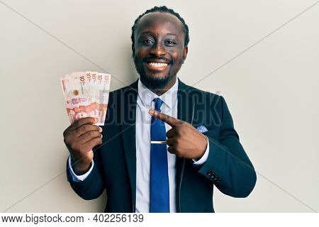 Handsome young black man wearing business suit holding 10 colombian pesos smiling happy pointing with hand and finger
