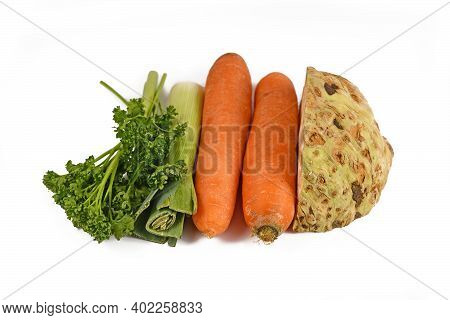 Bunch Of Soup Vegetables Containing Carrots, Leeks, Parsley And Celery Root Isolated On White Backgr