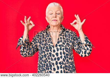 Senior beautiful woman with blue eyes and grey hair wearing casual and modern leopard animal print shirt relax and smiling with eyes closed doing meditation gesture with fingers. yoga concept.