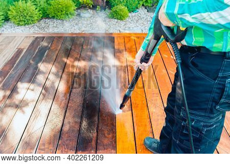 Power Washing - Worker Cleaning Terrace With A Power Washer - High Water Pressure Cleaner On Wooden