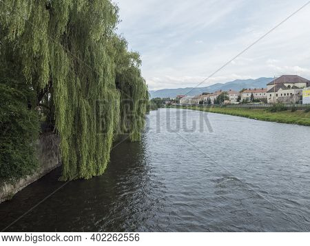Ruzomberok, Slovakia, August 30, 2020: View From Bridge On River Vah With Weeping Willow And Houses