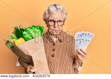 Senior grey-haired woman holding groceries and colombian pesos banknotes skeptic and nervous, frowning upset because of problem. negative person.