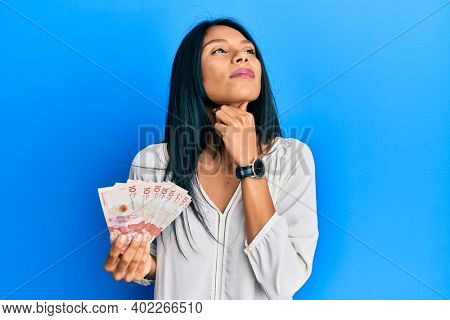Young african american woman holding 10 colombian pesos banknotes touching painful neck, sore throat for flu, clod and infection