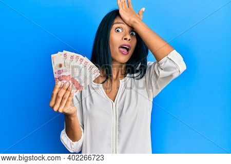 Young african american woman holding 10 colombian pesos banknotes surprised with hand on head for mistake, remember error. forgot, bad memory concept.