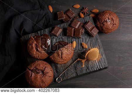 Homemade Muffins With Chocolate, Chocolate Bars And Almonds Grains On A Black Wooden Background. Coo